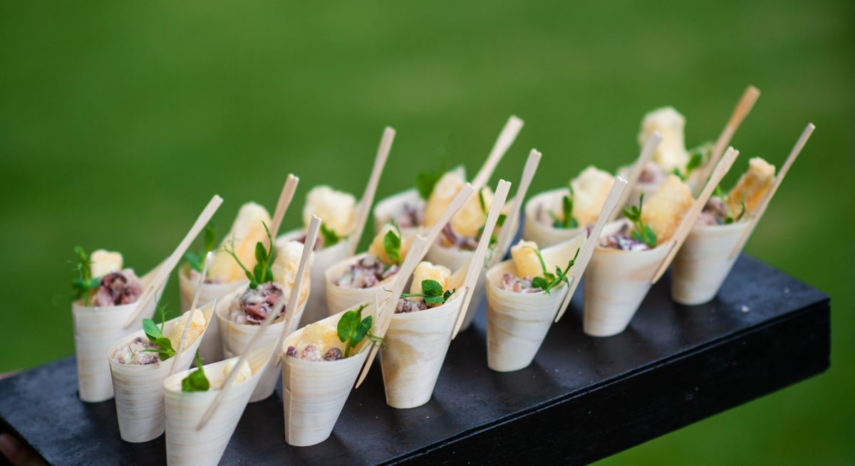 Fried Calamari Scampi Appetisers canapes being presented in bamboo cones and served at a party with selective focus.  It is being served at a wedding party.  A waiter is holding the tray with canapes.